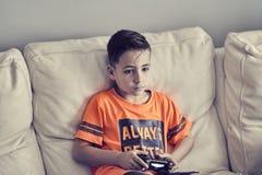 Jungen, die zu Hause Konsole spielen lizenzfreies stockbild