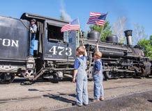 Jungen, die Zugingenieur der amerikanischen Flaggen wellenartig bewegen Stockbilder