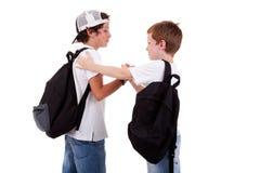 Jungen, die zur Schule, grüßend gehen stockfoto