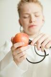 Jungen-Doktor Listening zu Apple mit Stethoskop Stockfotos