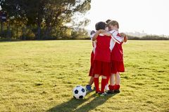 Jungen in einem Fußballteam, das im Team spricht, stecken vor Spiel die Köpfe zusammen lizenzfreie stockfotografie