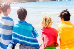 Jungen eingewickelt in den Badetüchern, die Sommermeer betrachten lizenzfreies stockfoto