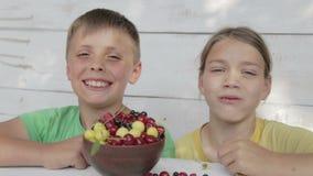 Jungen essen die frischen Beeren der Kirsche und der Korinthen stock footage