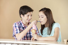 Jungen-Fütterungserdbeereis zur Schwester At Counter Lizenzfreie Stockfotografie