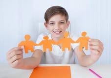 Jungen-Holding-Abbildungen der Papierfamilie in der Hand Lizenzfreie Stockfotos