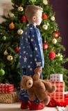 Jungen-Holding-Teddybär vor Weihnachtsbaum Stockfotos