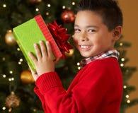 Jungen-Holding-Weihnachtsgeschenk vor Baum Stockfoto