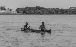Jungen in ihrem Kanu Stockbild