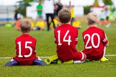 Jungen im Fußballteam, das zusammen auf dem Sportfeld sitzt stockbild