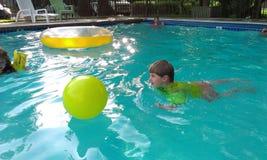 Jungen im Pool, das mit Ball spielt Stockbilder