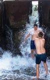 Jungen, Jugendliche spielen unter dem Wasserfall, im Fluss Naß und glücklich lizenzfreies stockbild