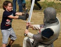 Jungen-kämpfender Ritter in der Rüstung Lizenzfreies Stockbild