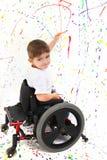 Jungen-Kind-Anstrich-Rollstuhl lizenzfreie stockfotografie