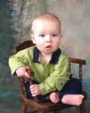 Jungen-Kind auf hölzernem Stuhl Stockfoto