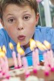 Jungen-Kind, das heraus Geburtstag-Kuchen-Kerzen durchbrennt Lizenzfreies Stockfoto