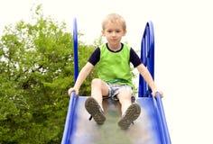 Jungen-Kind, das im Parkspielplatz spielt Lizenzfreies Stockfoto