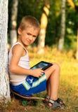 Jungen-Kind, das mit dem Tablet-PC sitzt auf dem Skateboard im Freien spielt Stockfoto