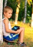 Jungen-Kind, das mit Tablet-PC spielt Stockbilder