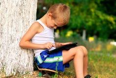 Jungen-Kind, das mit Tablette PC im Freien spielt Stockbilder