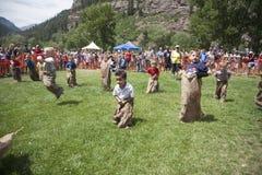 Jungen konkurrieren in drei mit Beinen versehen Stockfotos