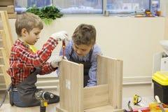 Jungen konstruieren hölzernen Schemel lizenzfreie stockbilder
