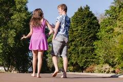 Jungen-Mädchen, das weg sprechend geht Lizenzfreie Stockfotos
