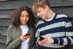 Jungen-Mädchen-männlich-weibliche Jugendliche, die Handy verwenden Stockfotos