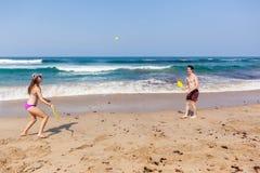 Jungen-Mädchen-Strand-Ozean-Schläger-Ball-Freizeit Stockbild