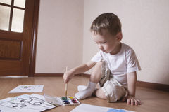 Jungen-Malerei mit Aquarellen und Malerpinsel Stockbilder