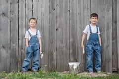 Jungen mit Bürsten und Farbe an einer alten Wand Stockbilder