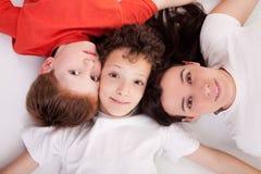 Jungen mit der Frau, liegend auf dem Fußboden mit Köpfen lizenzfreies stockfoto