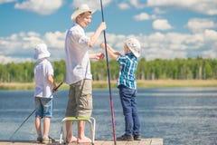 Jungen mit seinem Vater auf dem Pier bei der Fischerei Lizenzfreie Stockbilder