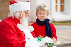 Jungen-Nehmen vorhanden von Santa Claus Lizenzfreie Stockfotografie