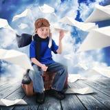 Jungen-Pilot mit den Papierflugzeugen, die in Himmel fliegen Stockfotografie