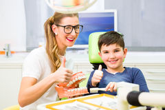 Jungen-Reinigungszahn des Zahnarztes erklärender Lizenzfreie Stockfotografie
