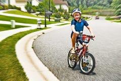 Jungen-Reitfahrrad in der Nachbarschaft Lizenzfreies Stockfoto