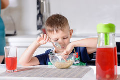 Jungen-Sammeln am Hafermehl-Getreide zur Frühstückszeit Stockbild