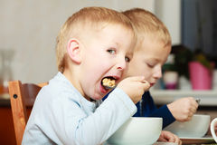 Jungen scherzt die Kinder, die Corn- Flakesfrühstücksmahlzeit am Tisch essen Stockbilder