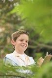 Jungen-Schreiben auf Klemmbrett im Wald lizenzfreie stockbilder