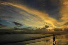 Jungen-Spiel auf dem Strand an der Dämmerung mit drastischem Sonnenuntergang-Himmel Lizenzfreie Stockbilder