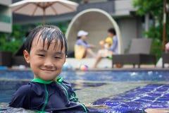 Jungen spielten im Swimmingpool Stockfotos