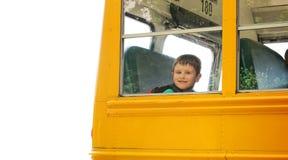 Jungen-steigender Schulbus auf weißem Hintergrund Stockfoto