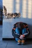 Jungen-Teenager, der auf dem Fußboden alleine in der Stadt sitzt stockbilder