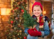 Jungen-tragender Schal im Weihnachten verzierte den Raum, der kleinen Baum hält Lizenzfreies Stockfoto