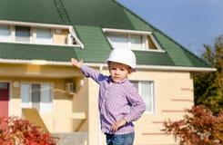 Jungen-tragender Schutzhelm, der fertiges Haus darstellt Stockfotografie
