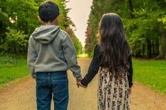 Jungen-u. Mädchen-Händchenhalten, das Weg gegenüberstellt, um zu überholen Stockfotos