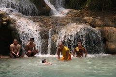 Jungen und ein buddhistischer Mönch des Anfängers genießen, im Wasserfall, La zu baden Lizenzfreie Stockbilder