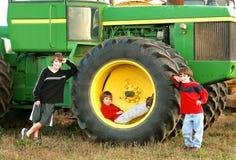 Jungen und ein großer Traktor Lizenzfreies Stockfoto