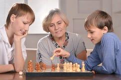 Jungen und Großmutter, die Schach spielen lizenzfreie stockbilder
