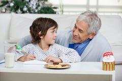 Jungen-und Großvater-Schreibens-Buchstabe zu Santa Claus Lizenzfreies Stockfoto